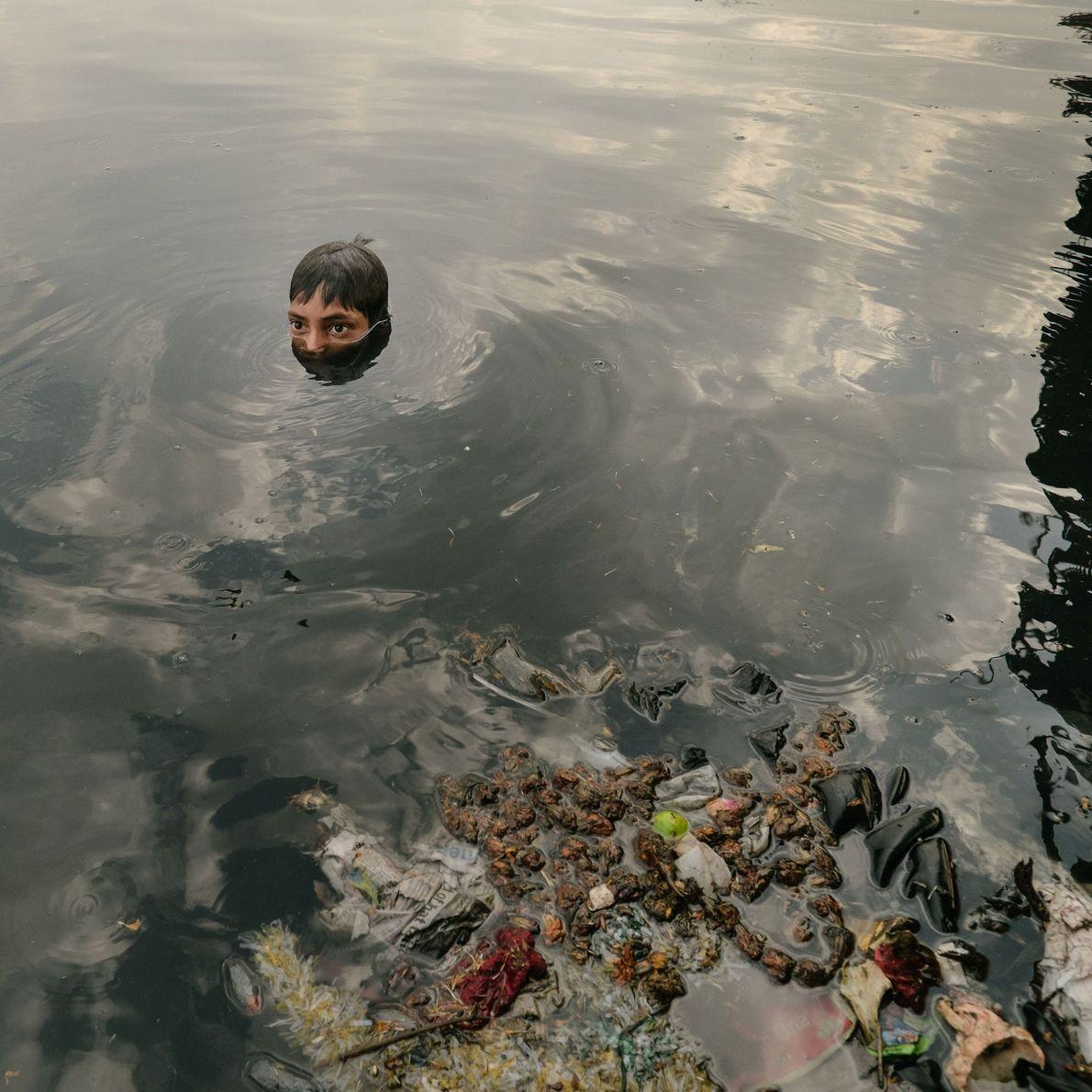 crianças buscam por metal em lixo no rio