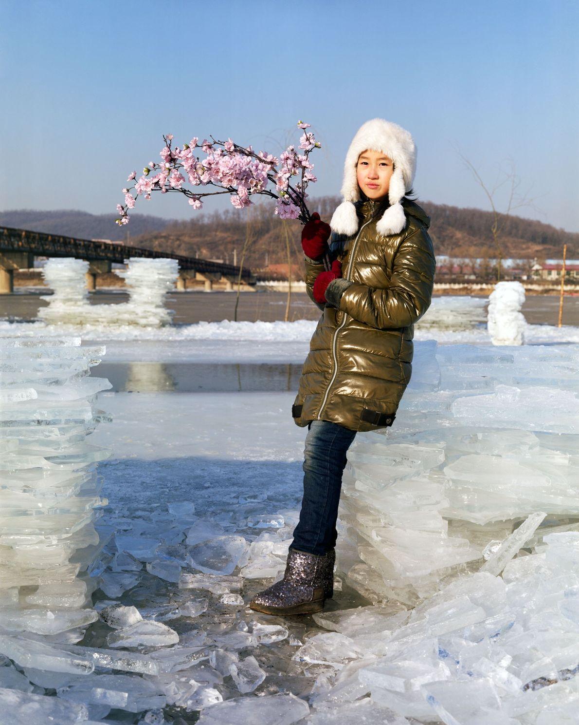 Yuting, de 10 anos, em pé na margem do rio Hun com um buquê de flores ...