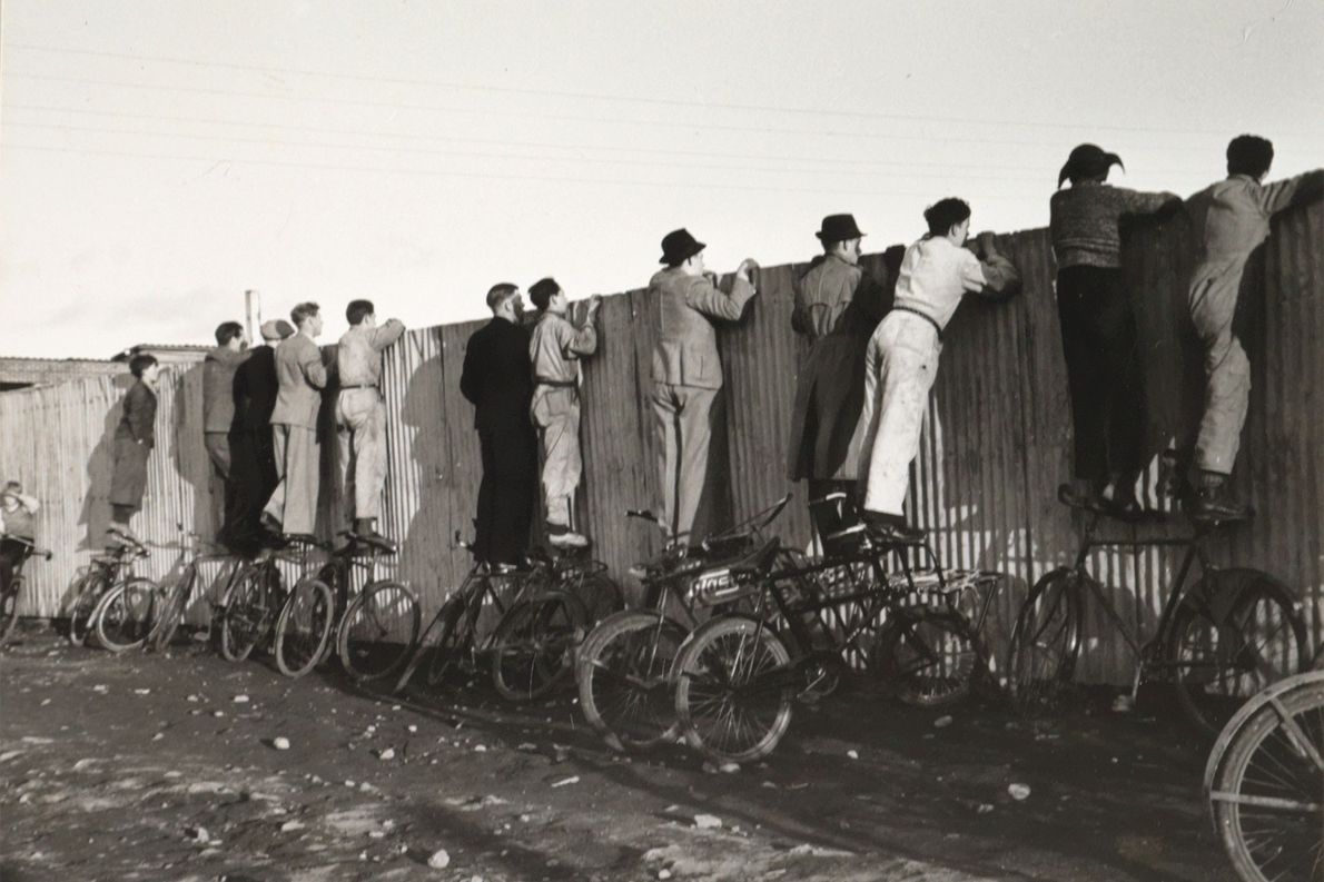Se equilibrando em bicicletas, islandeses olham por cima de uma cerca para assistir a um jogo ...
