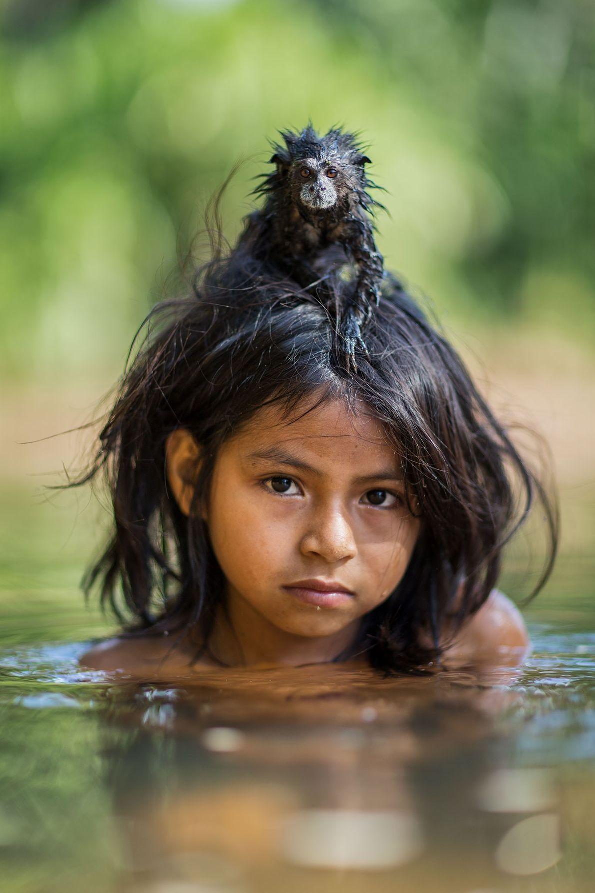 A pet saddleback tamarin hangs on tight to Yoina Mameria Nontsotega as the Matsigenka girl takes ...