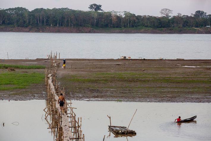 Uma longa passarela conecta Puerto Alegría ao rio Amazonas. Do outro lado do rio fica a ...