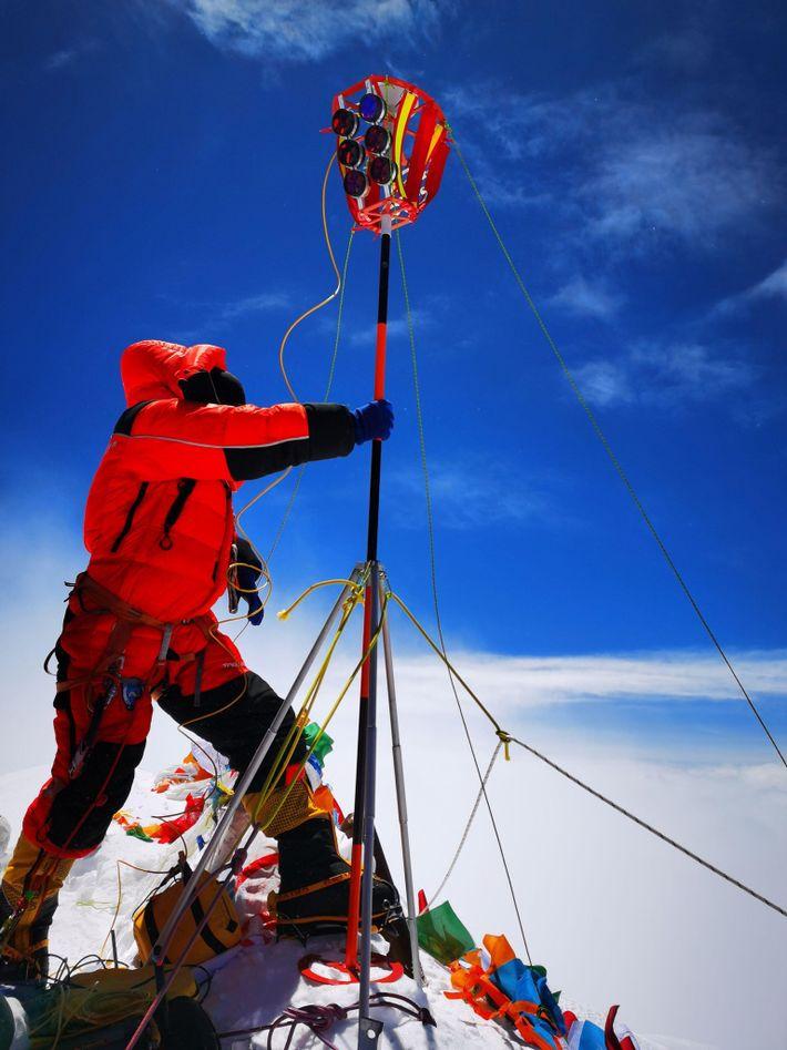 Membro da equipe chinesa de levantamento instala um marcador no pico do Monte Everest em 27 ...