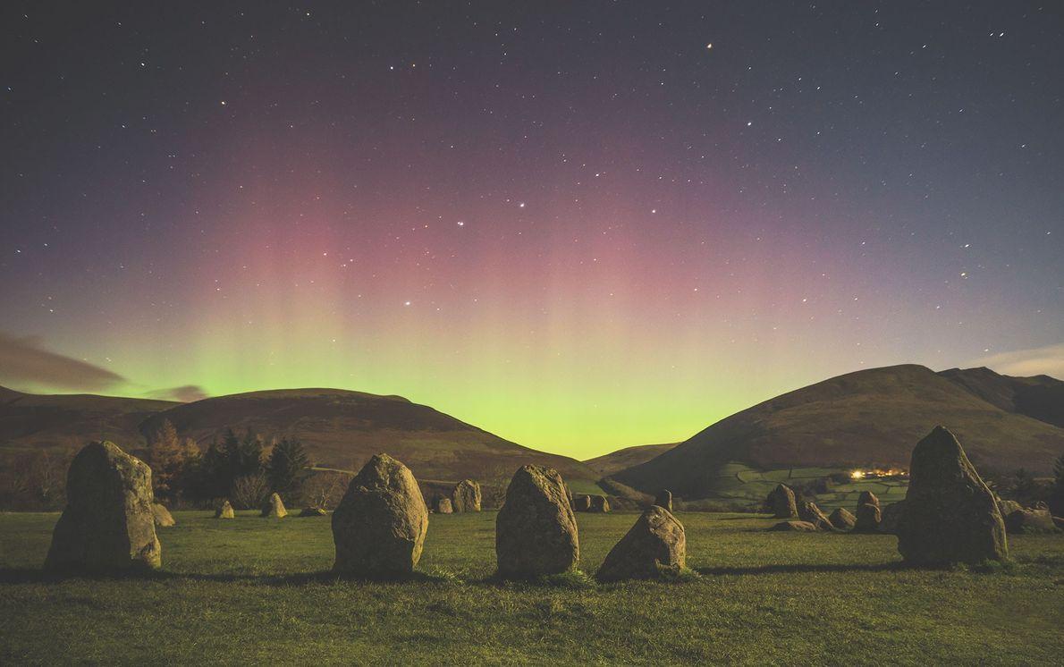 A aurora boreal ilumina as colinas à margem do círculo de pedra de Castlerigg em Cumbria, ...