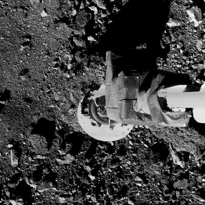 Em uma simulação, o braço de amostragem da sonda OSIRIS-REx é abaixado até perto da superfície ...