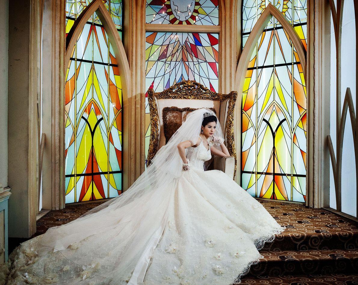 Pan, 33, que trabalha como designer de moda, posa em um vestido de casamento estilo ocidental.