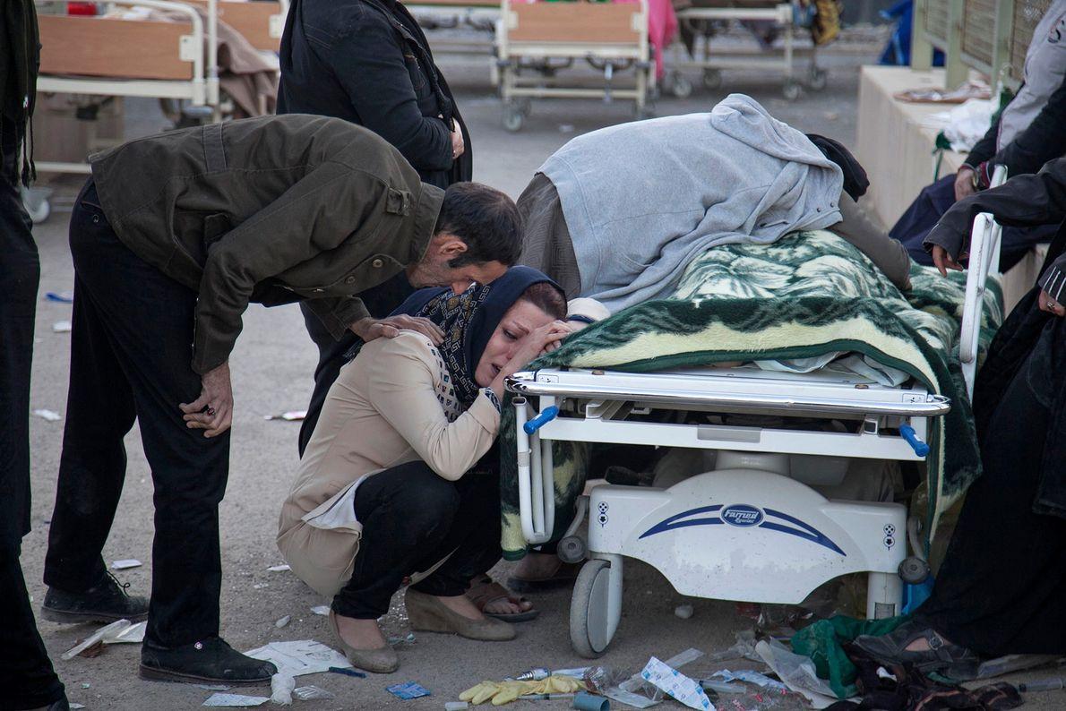 família chorando sobre corpo de vítima do terremoto