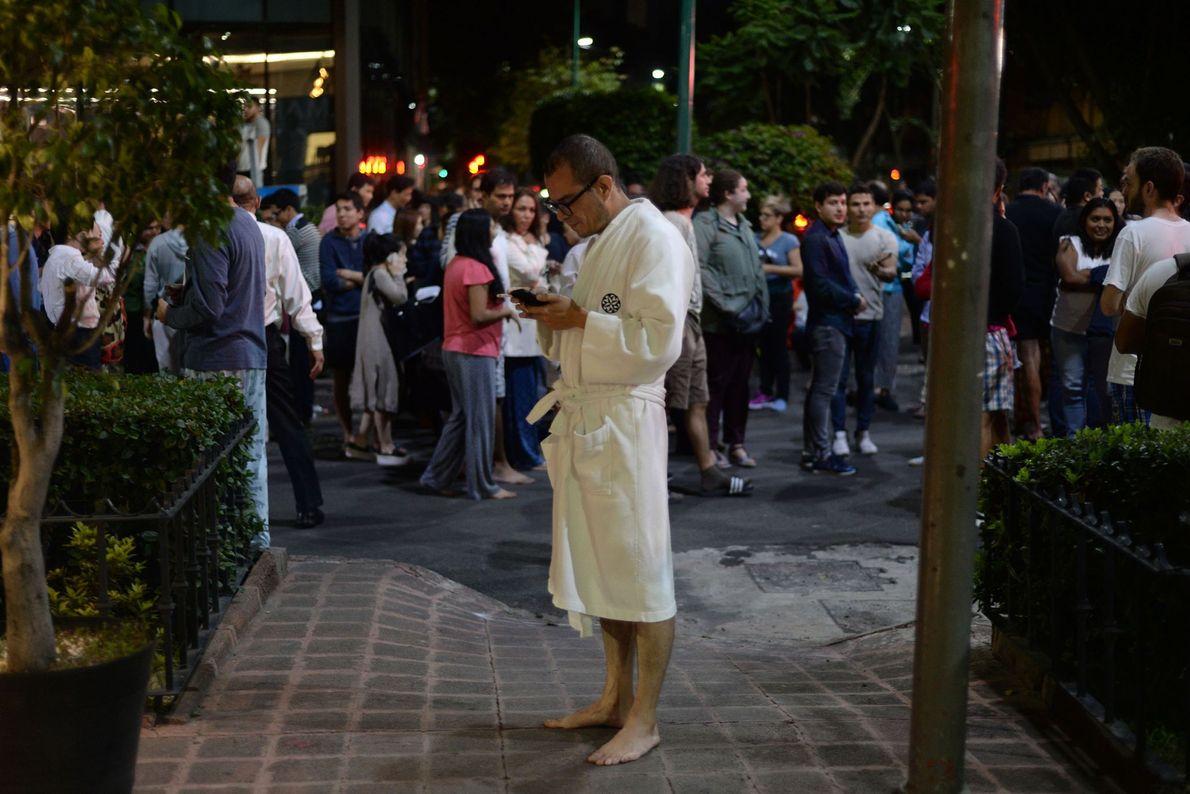 As pessoas se reúnem em uma rua no centro da Cidade do México. O terremoto foi ...