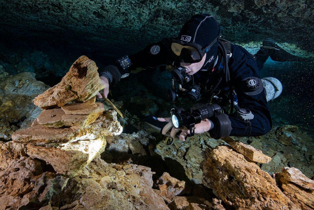 Um mergulhador examina pedras empilhadas por antigos mineiros que extraíam o pigmento ocre de La Mina, ...
