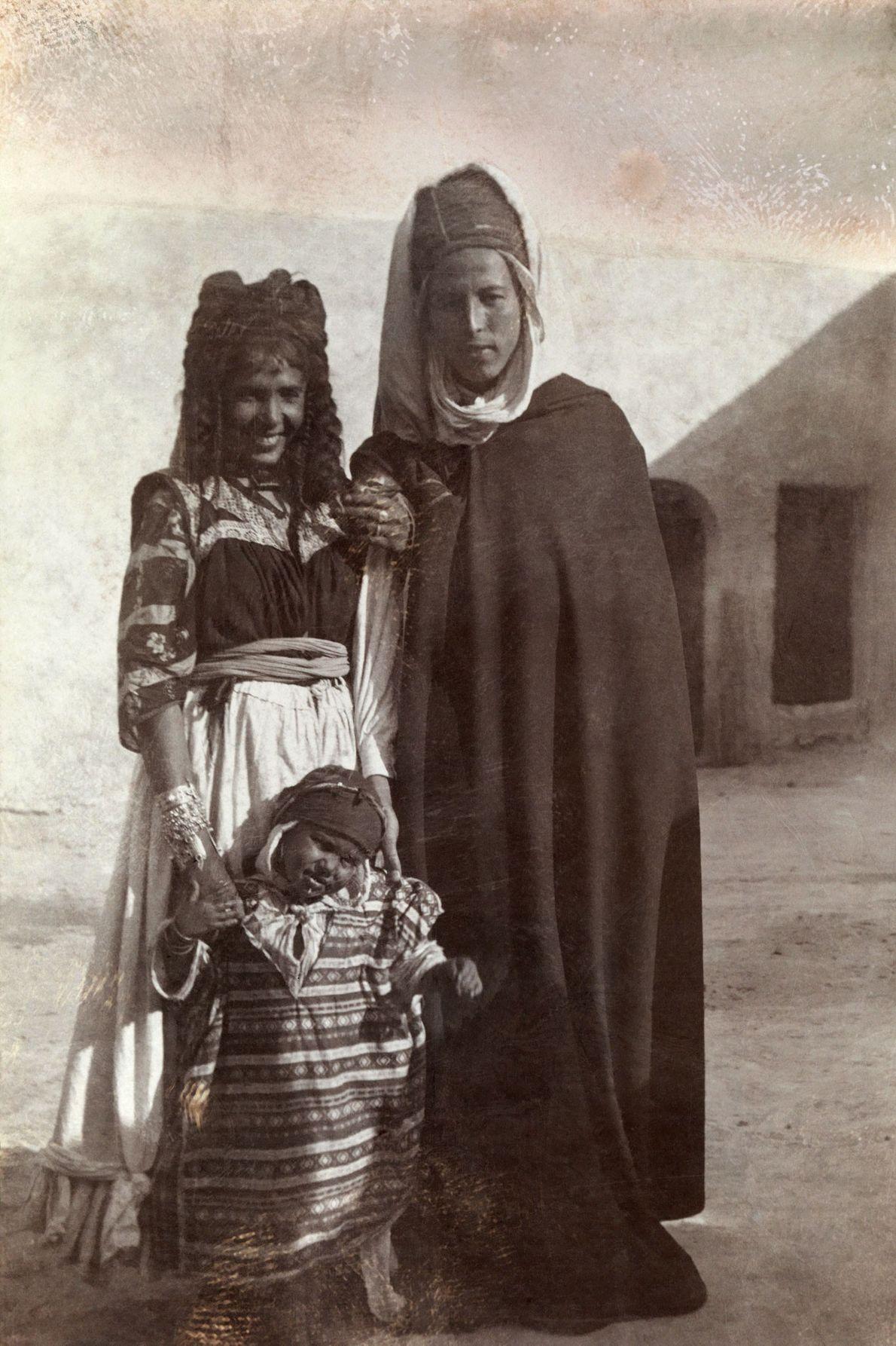 Um jovem casal algeriano em Biskra de pé com seu filho em frente a um prédio.