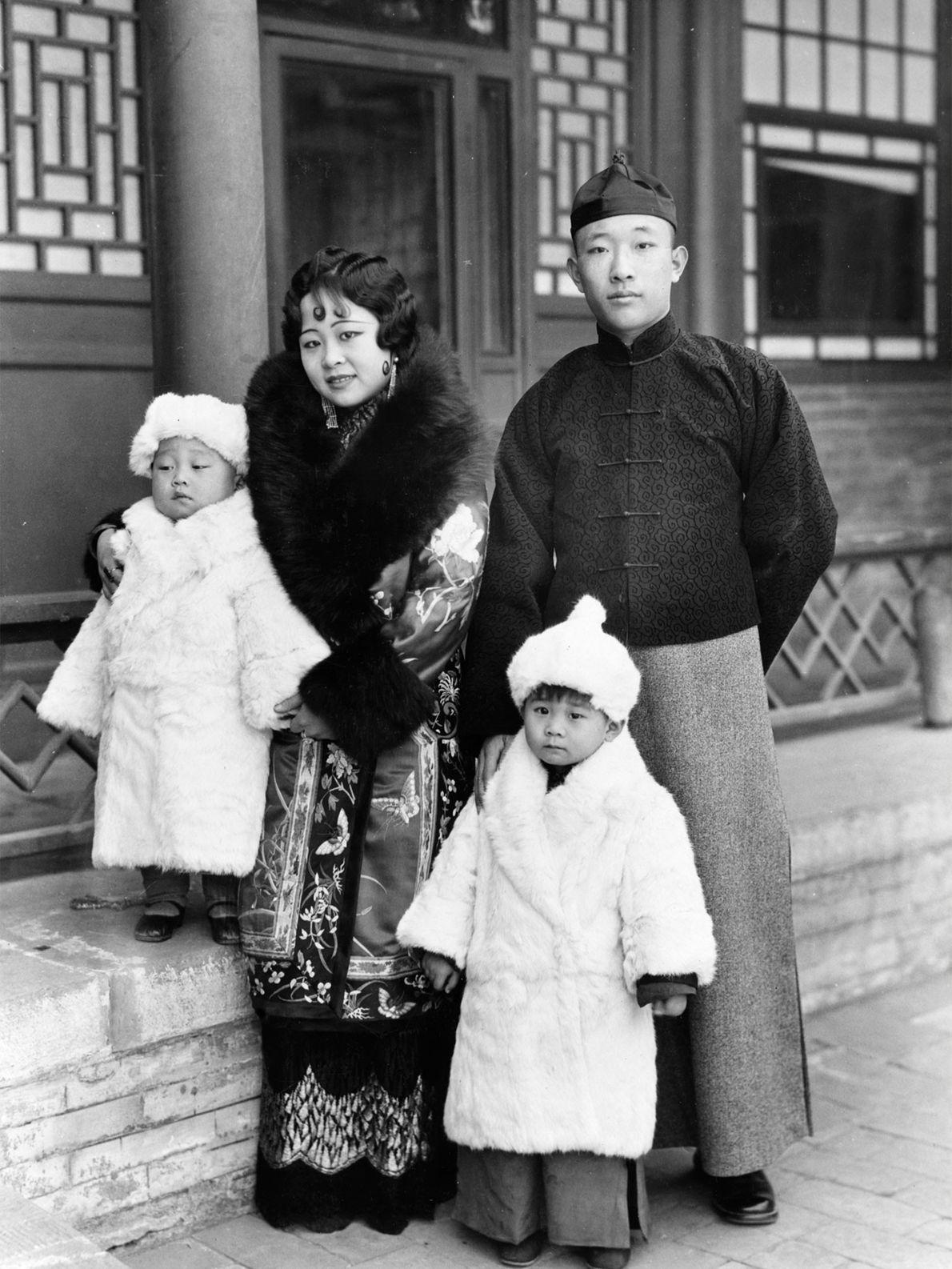 Um príncipe e uma princesa da Mongólia de pé com seus filhos pequenos, envoltos em peles ...