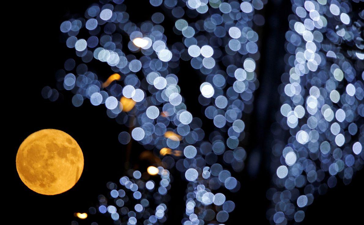 A lua cheia é retratada atrás das luzes de Natal em Marselha, França.