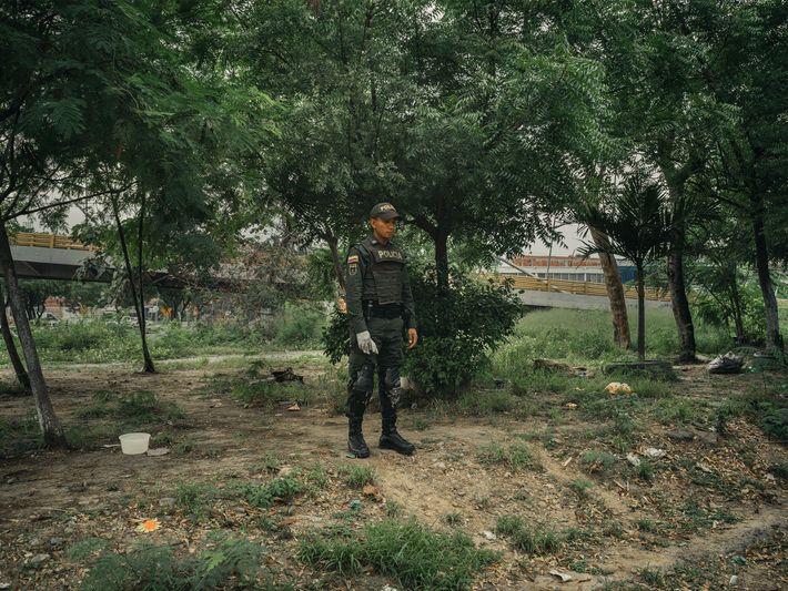 Um policial está em um parque ao lado do Canal de Bogotá, em Cúcuta, na Colômbia, ...