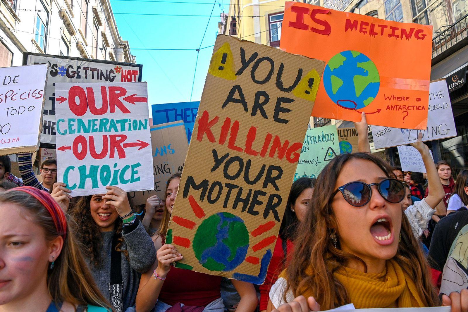 Estudantes portugueses entoam gritos de protesto e exibem cartazes em frente ao Parlamento de Portugal.