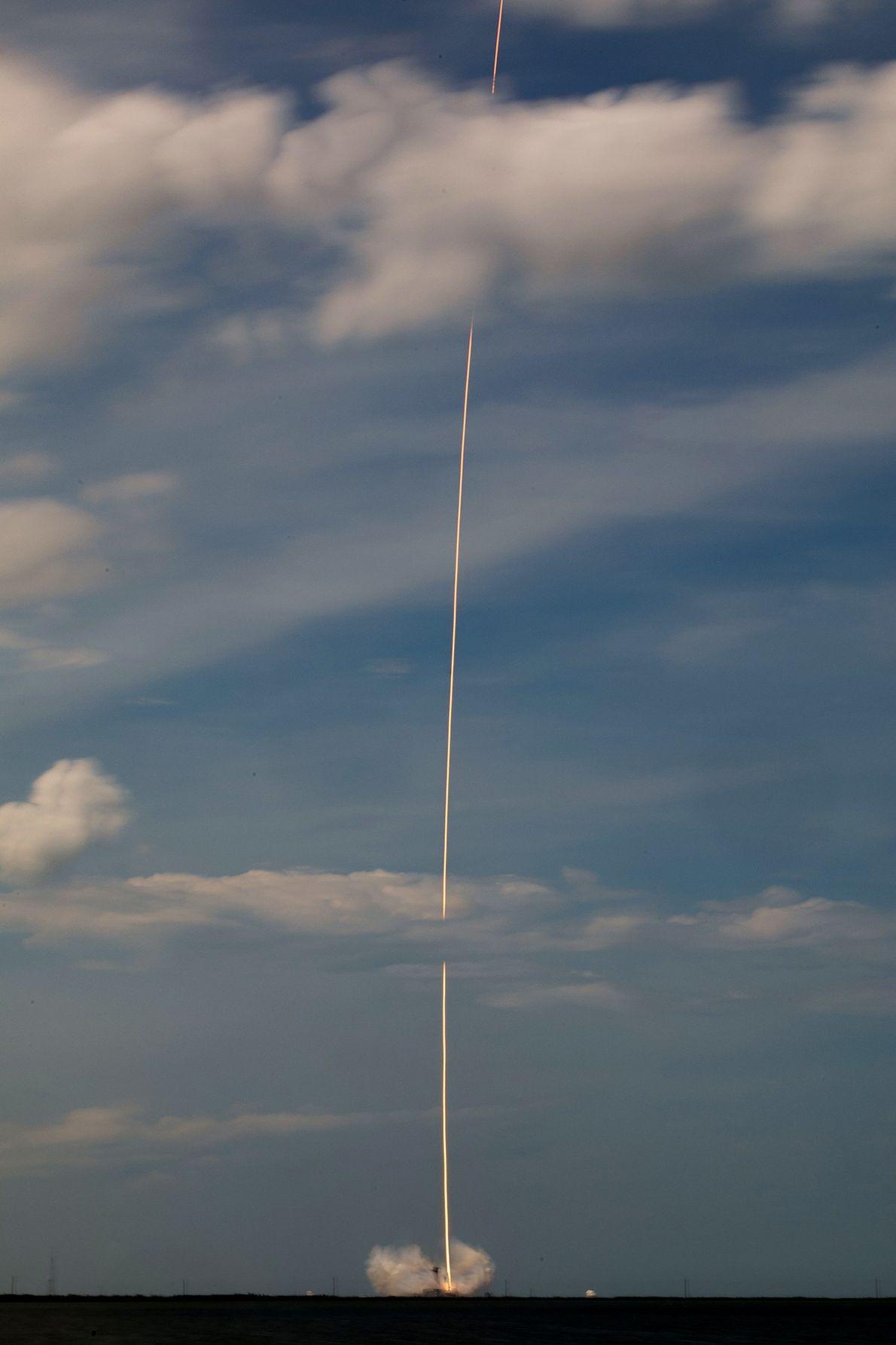 Uma chama laranja e brilhante do foguete SpaceX Falcon 9 parece traçar uma linha por entre ...