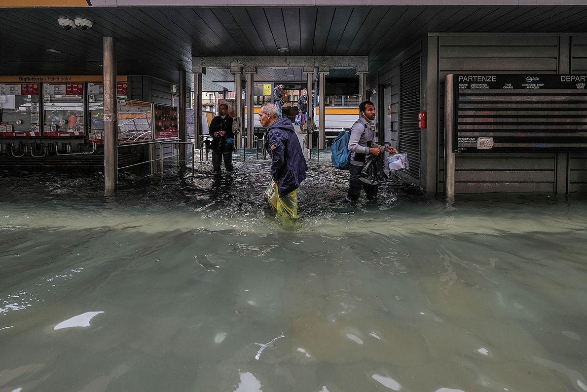 Turistas caminham em frente a um ponto de parada. As escolas e os hospitais de Veneza ...