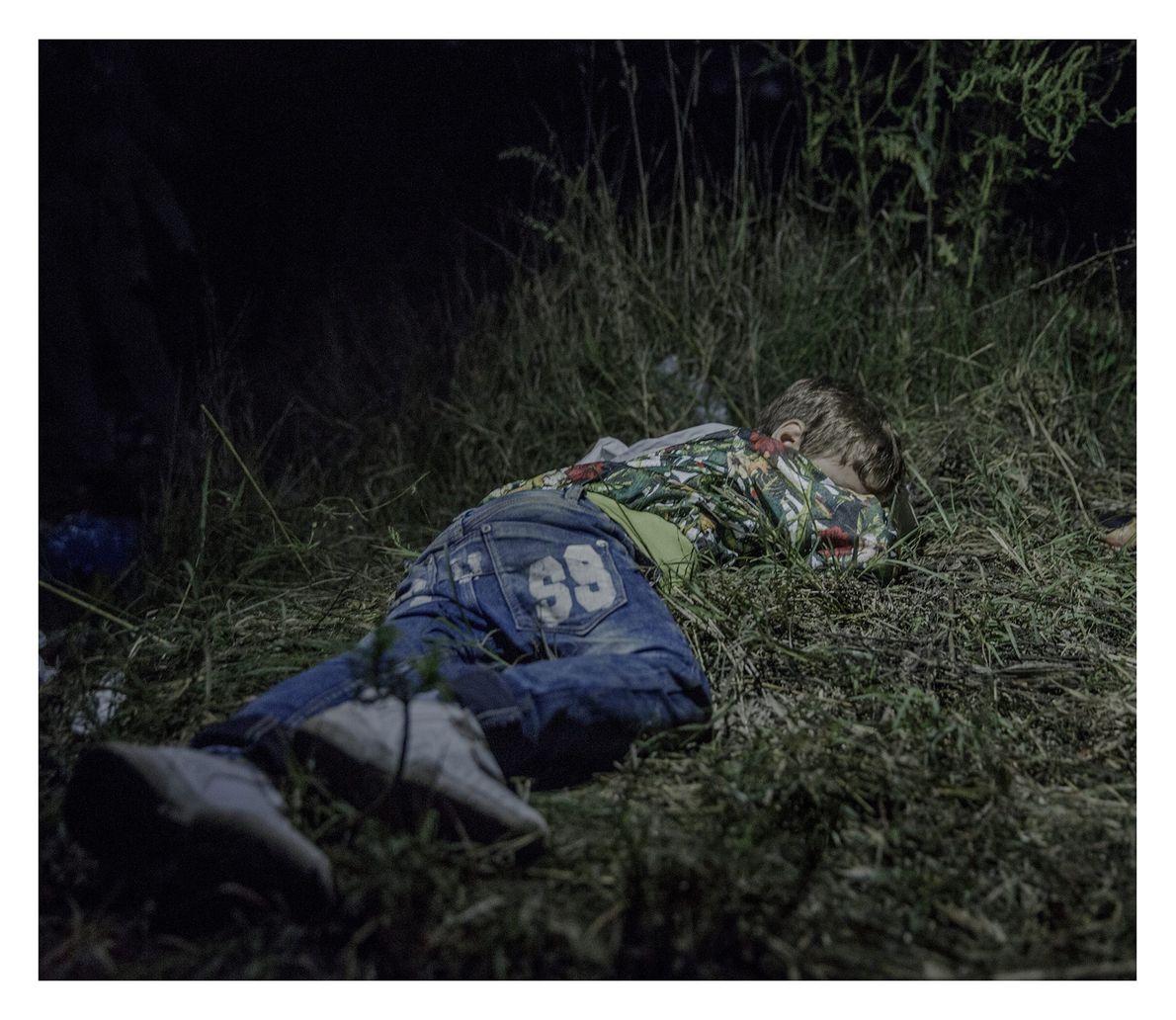 Criança refugiada dormindo na grama