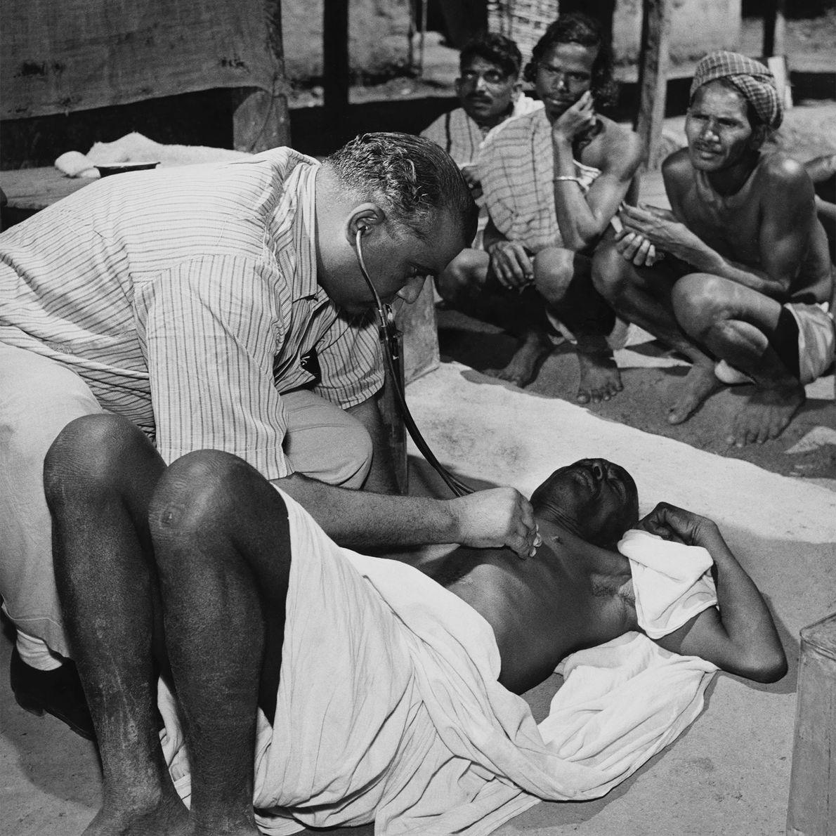 Pacientes observam um médico examinar um paciente no povoado de Bastar.