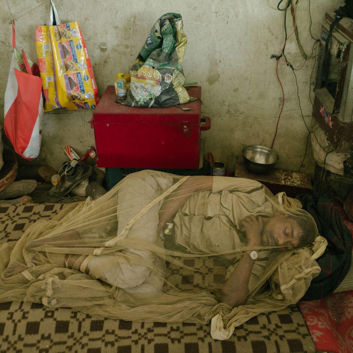 homem dorme próximo a rio poluído e se protege de doenças como dengue