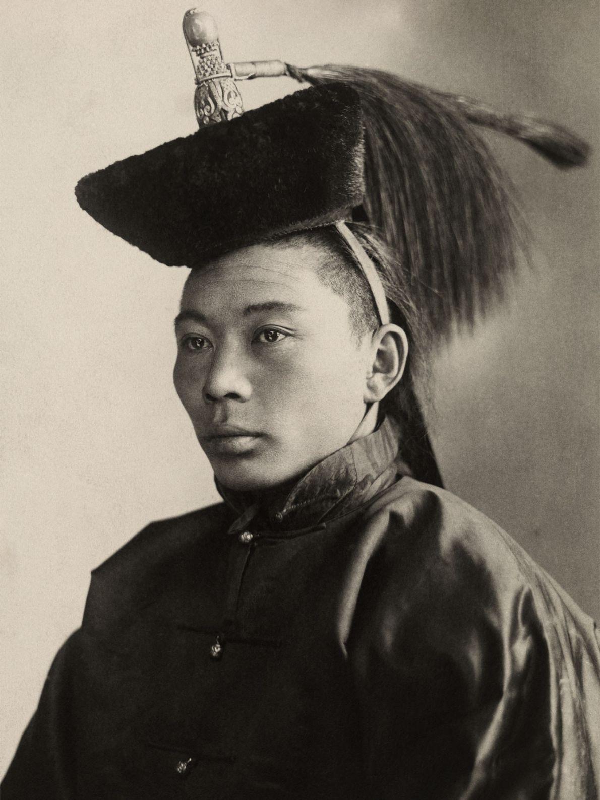 Um jovem príncipe da Mongólia posa para uma foto, usando um chapéu com enfeites que simbolizam ...