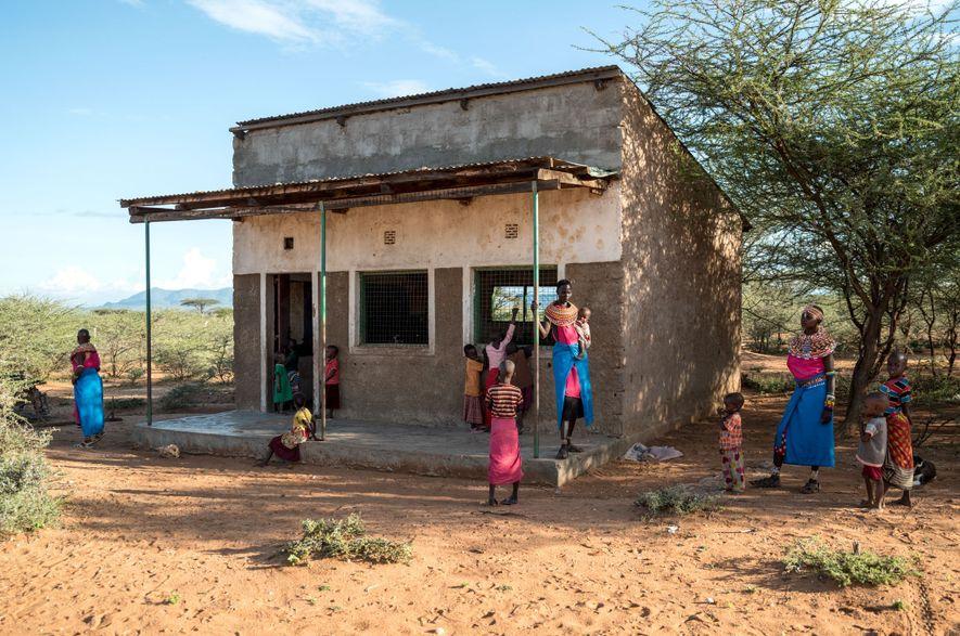 As mulheres Samburu esperam em frente a uma sala de aula para começar uma aula de ...