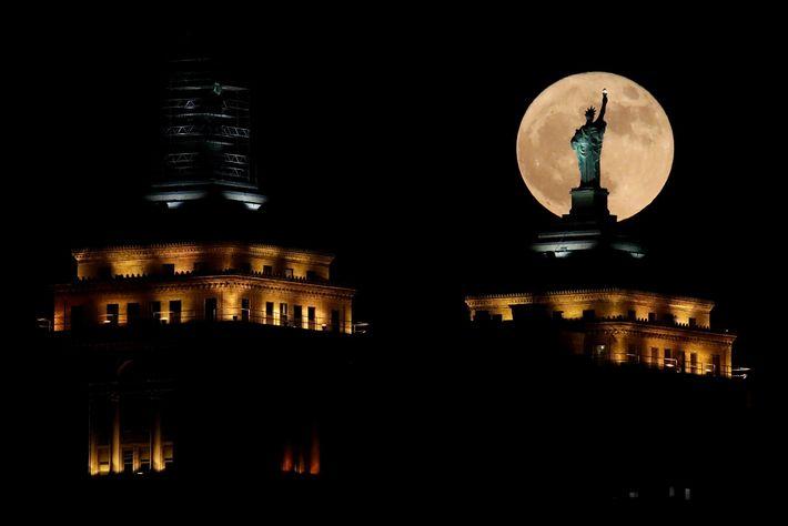 Um superlua nasce diante de uma réplica da Estátua da Liberdade, sentada no topo do Edifício ...