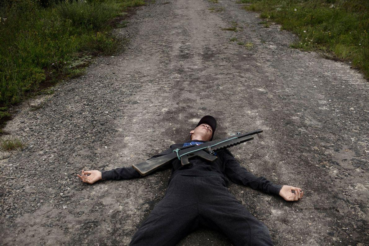"""Um menino ucraniano deita no chão fingindo ter sido morto por """"fogo inimigo"""" durante um treinamento ..."""