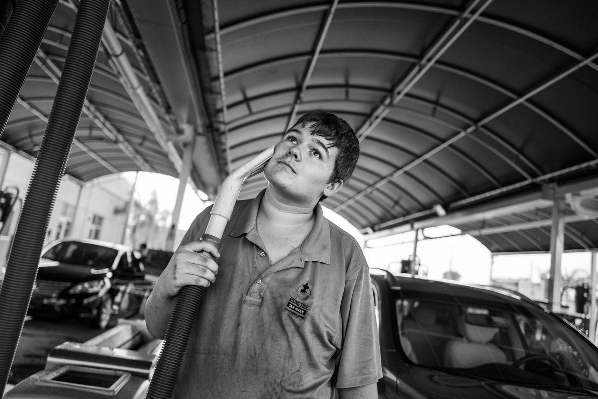 Luke Zenda, de 19 anos, passando o bocal do aspirador em sua bochecha no lava-jato Rising ...