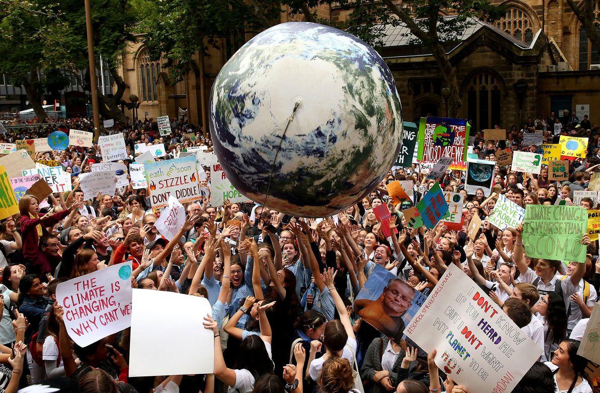 Manifestantes jogam um planeta Terra inflável na multidão durante o evento de conscientização sobre as Mudanças ...