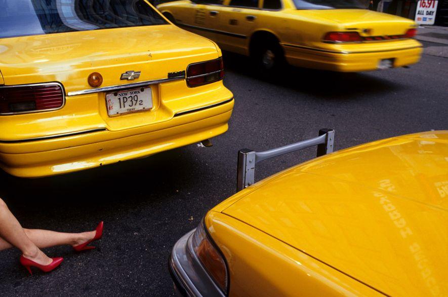 Pernas de uma mulher, usando salto alto vermelho, e táxis passando na Times Square.