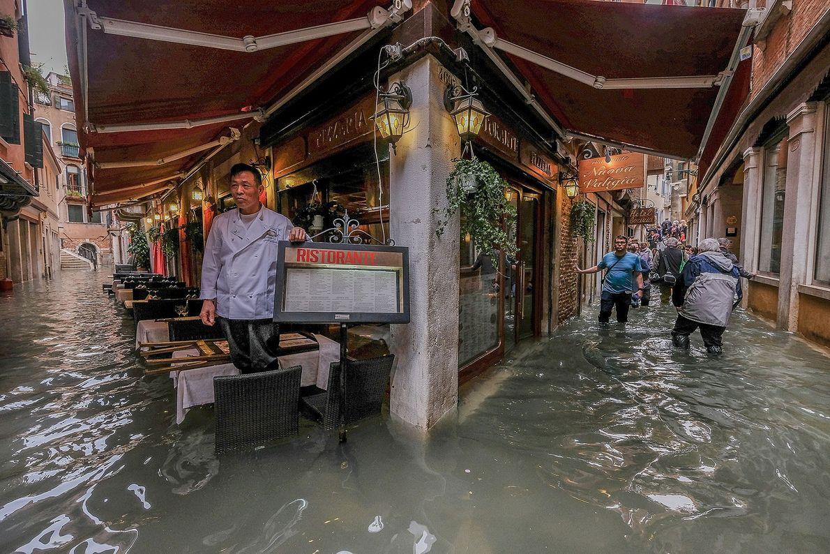 Dono de restaurante observa as ruas inundadas.