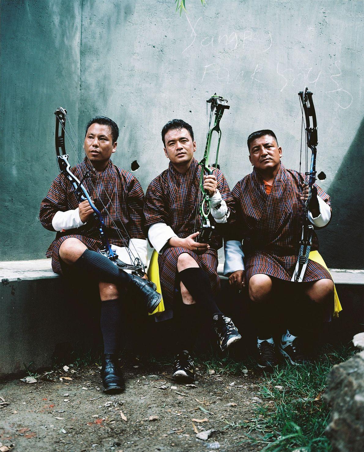 Três homens descansam durante uma competição local de arco e flecha em Paro. Da esquerda para …
