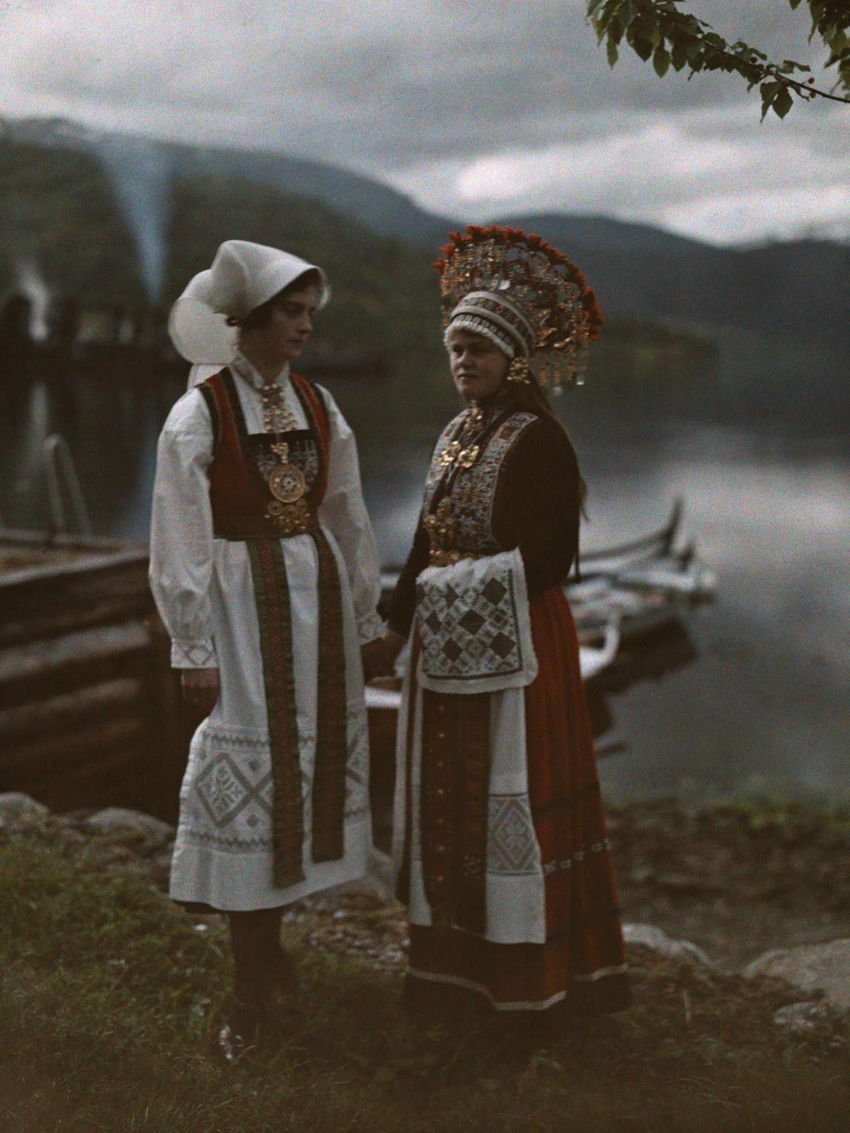 Uma mulher casada e uma noiva posam para foto em vestidos tradicionais. Ulvik, Noruega.