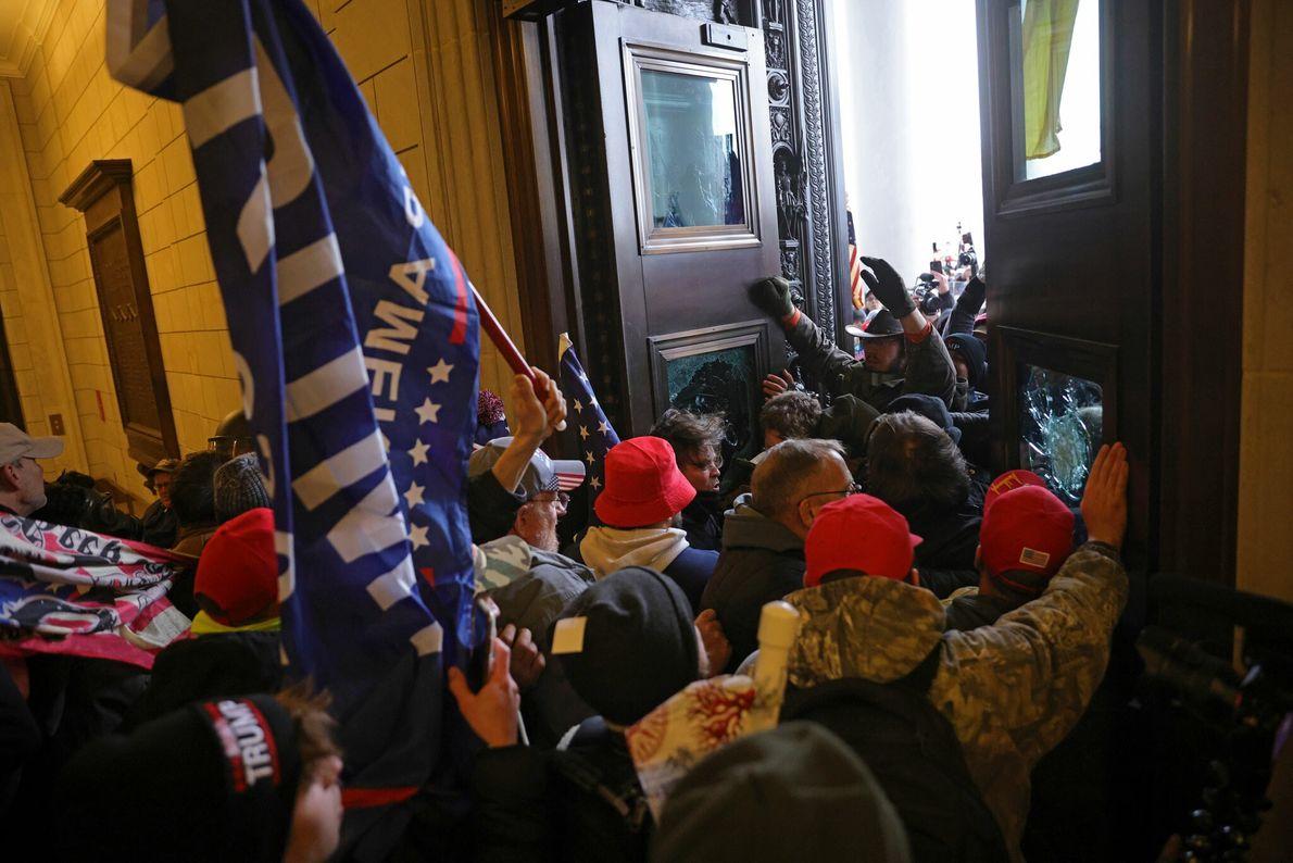 Vândalos carregando bandeiras de Trump arrombaram as portas do capitólio dos EUA, entrando no perímetro de ...