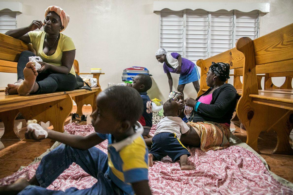 Famílias se reúnem em um abrigo em uma igreja local durante a noite antes da chegada ...