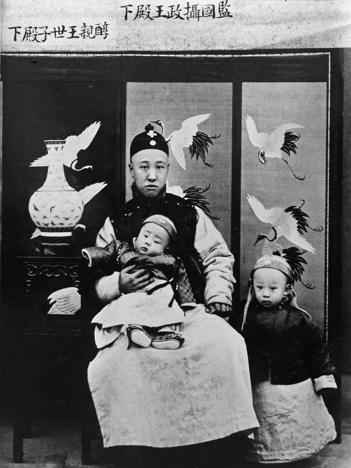 O Príncipe Chun, um regente da China, segura seu filho, o Imperador Xuantong, na província de ...