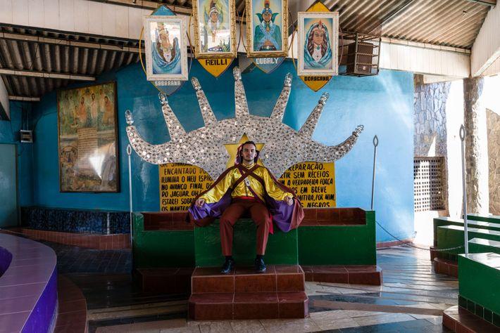 Um seguidor do Vale do Amanhecer – vestido com um traje de príncipe maia – senta-se ...