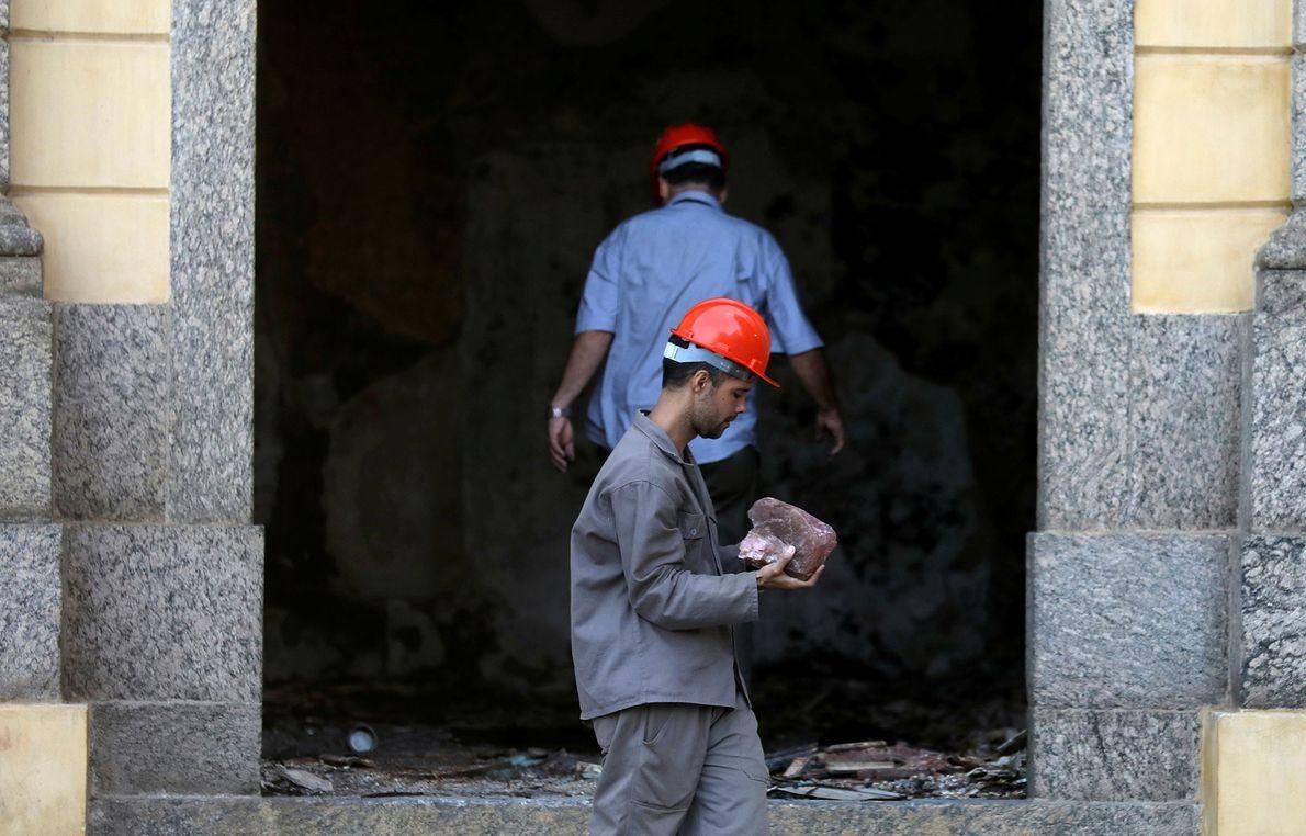 Funcionário carrega um pedaço de rocha encontrada dentro do Museu Nacional.