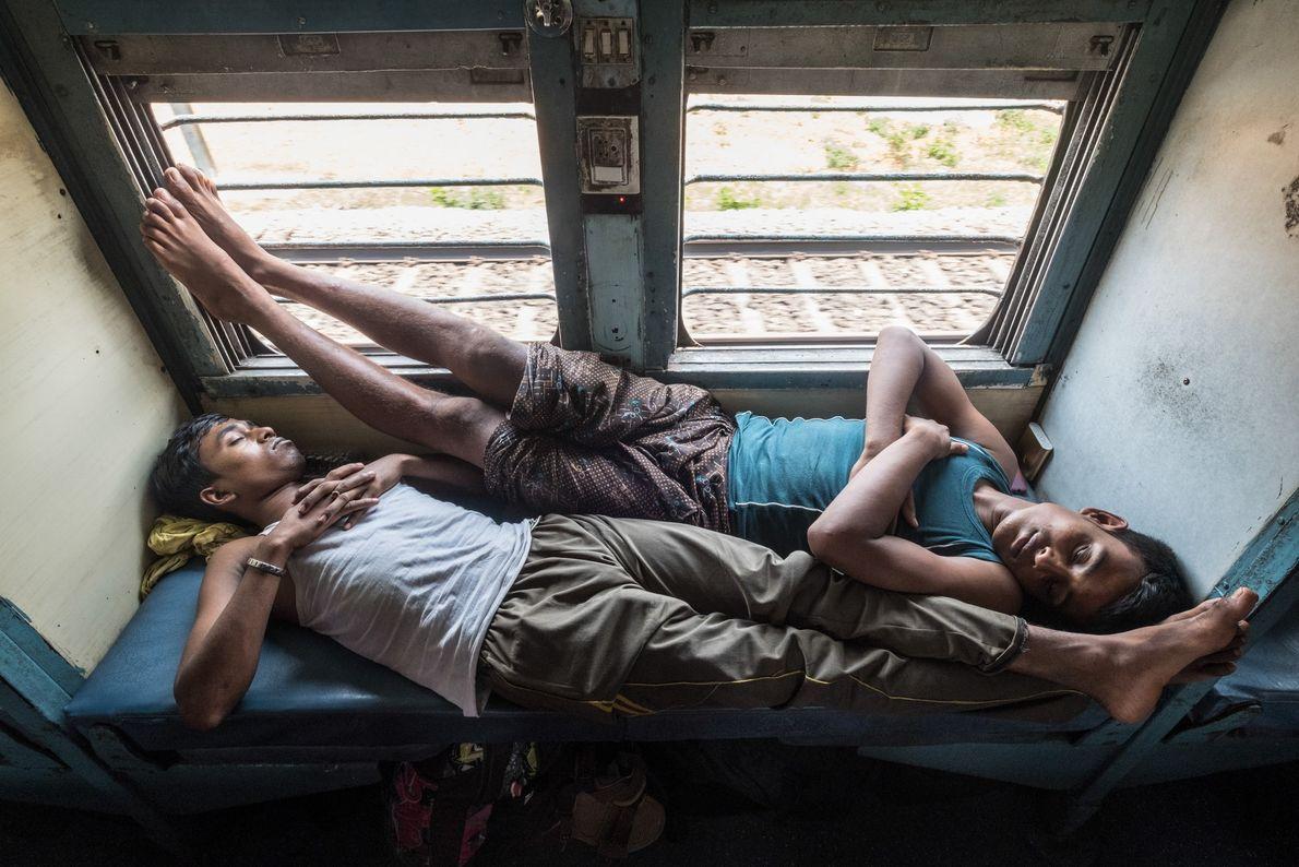 Passageiros, em sua maioria pedreiros, tiram um cochilo enquanto voltam para casa no nordeste da Índia, ...