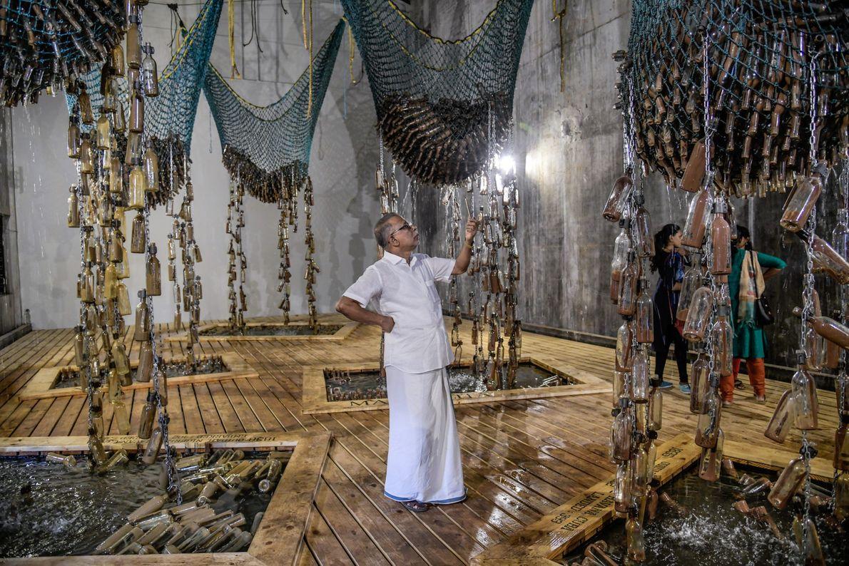 """Fort Kochi, Índia Visitantes observam a instalação """"Messages from the Atlantic Passage"""" (Mensagens da Passagem do Atlântico, ..."""