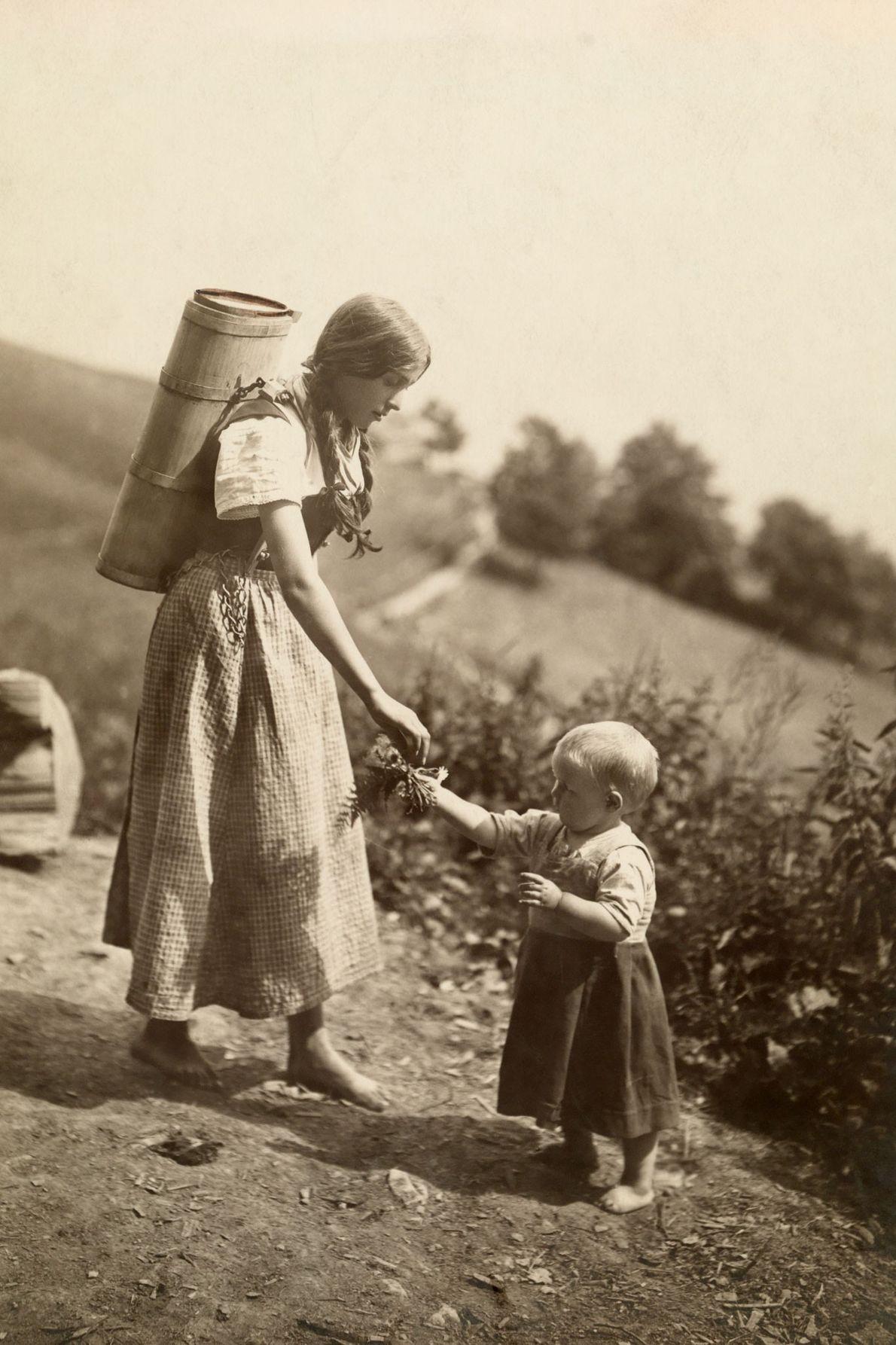 Uma mãe suíça indo ao encontro da mão de sua filha, que está cheia de flores.