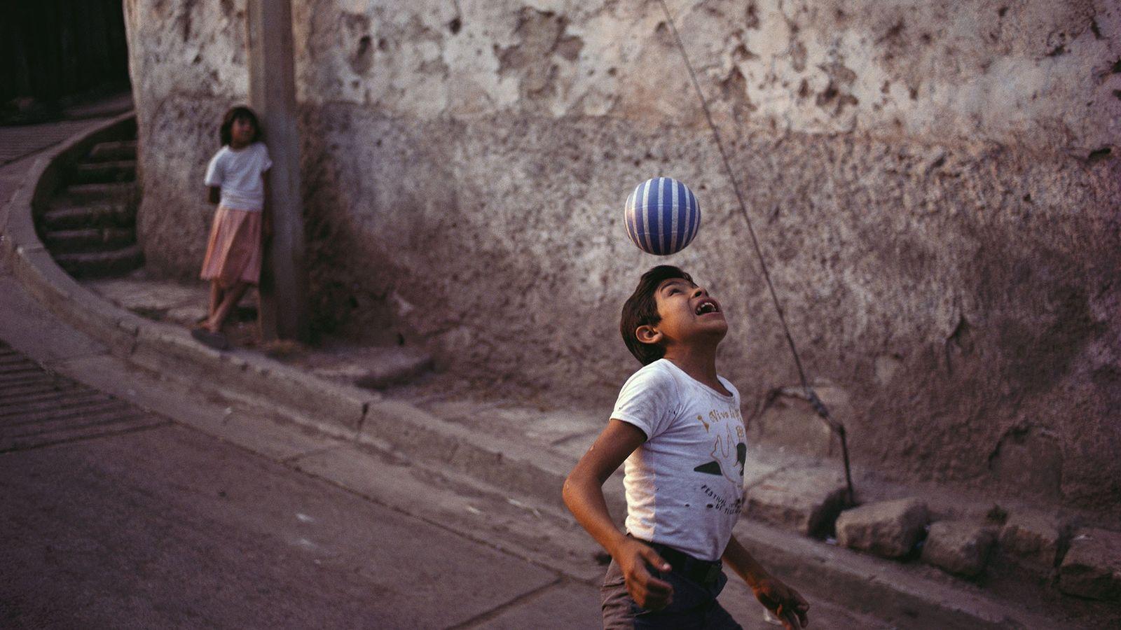 Um menino pratica suas habilidades futebolísticas em uma rua em Tegucigalpa, Honduras. A popularidade do futebol ...