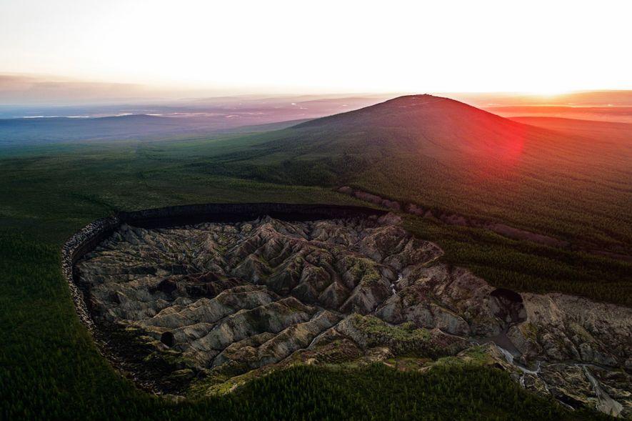 """A Cratera Batagaika na cidade de Batagay, na Rússia, é conhecida como a """"cratera do inferno"""" ou o """"portal para o submundo."""" Com mais de 90 metros de profundidade e mais de 800 metros de comprimento, a depressão é uma das maiores do mundo. Cientistas acreditam que ela começou a se formar nos anos 1960, quando o permafrost sob a área começou a derreter após o desmatamento das florestas vizinhas."""