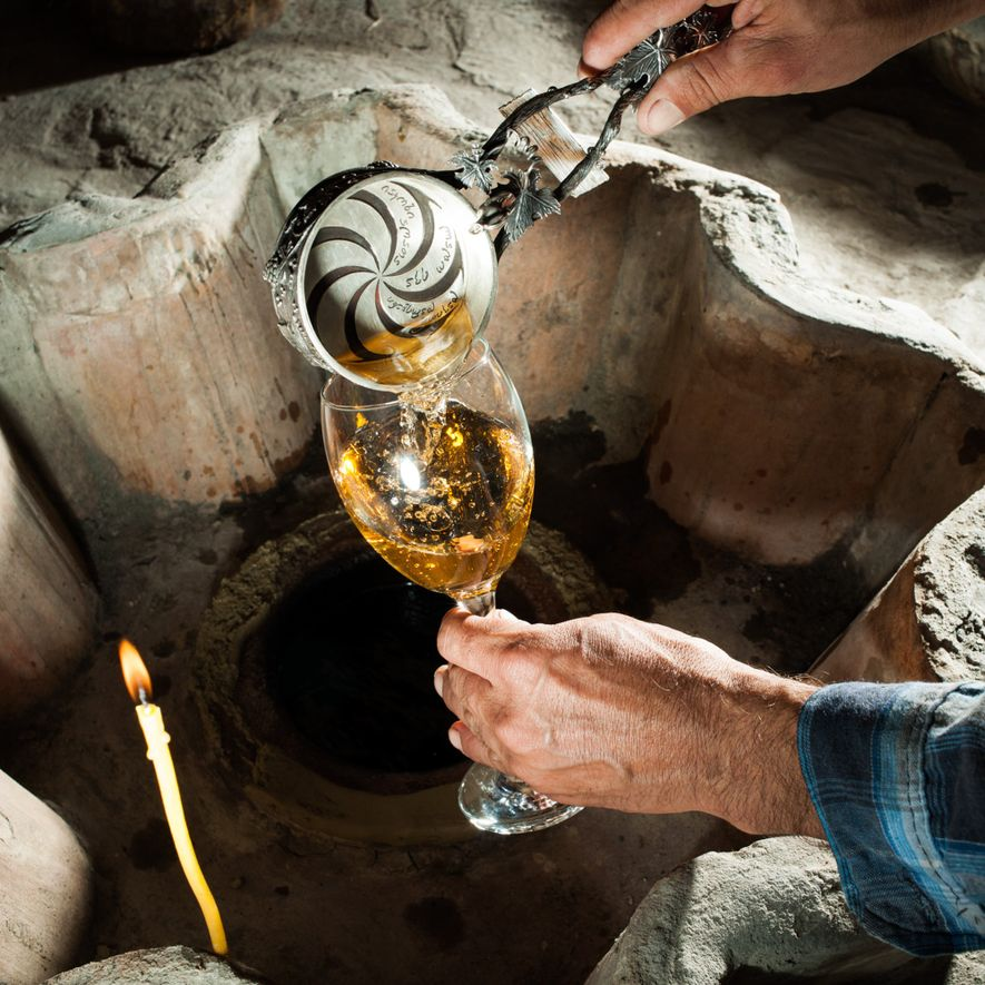 A produção de vinho tem raízes profundas na Geórgia, onde um vinicultor serve um vinho branco ...