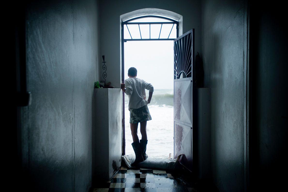 Um residente de Saint-Pierre, na ilha caribenha francesa da Martinica, espera à porta enquanto olha para ...