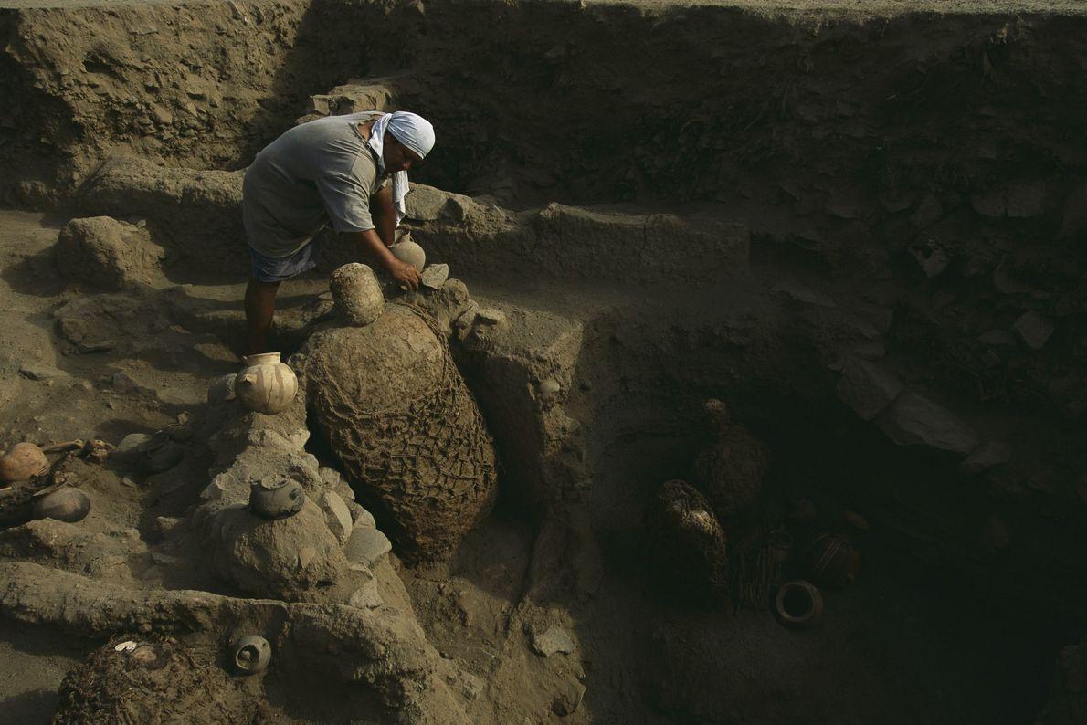 Um arqueólogo remove artefatos próximos a uma múmia inca. Milhares de múmias com 500 anos contêm …