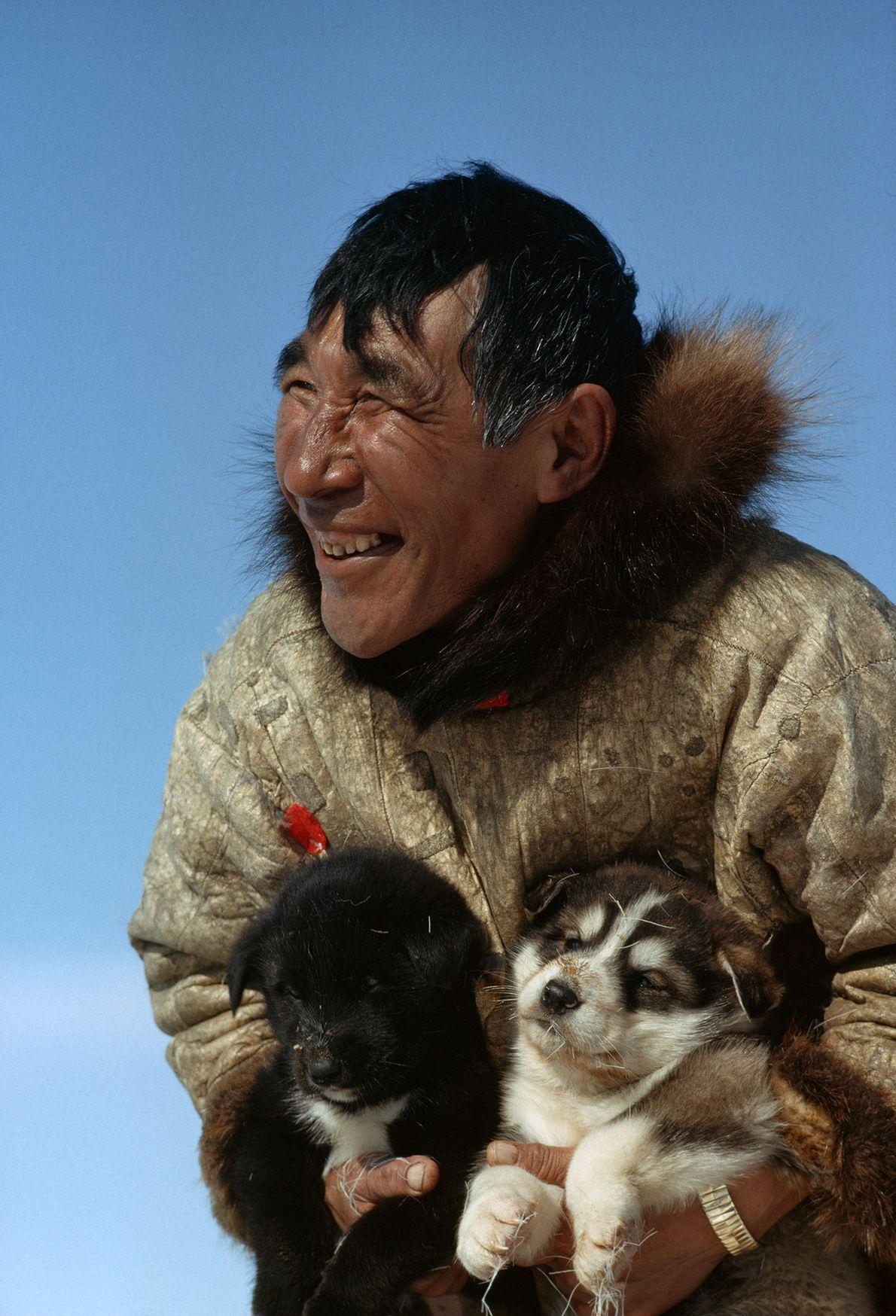 Homem segura um filhote cujo destino é se tornar membro de uma valiosa equipe de cães ...