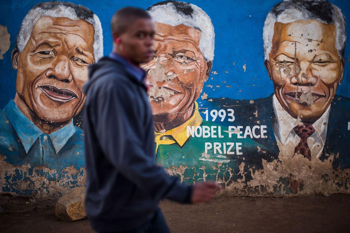 Homem passa por uma parede com várias imagens de Nelson Mandela na rua Khumalo em Soweto, ...