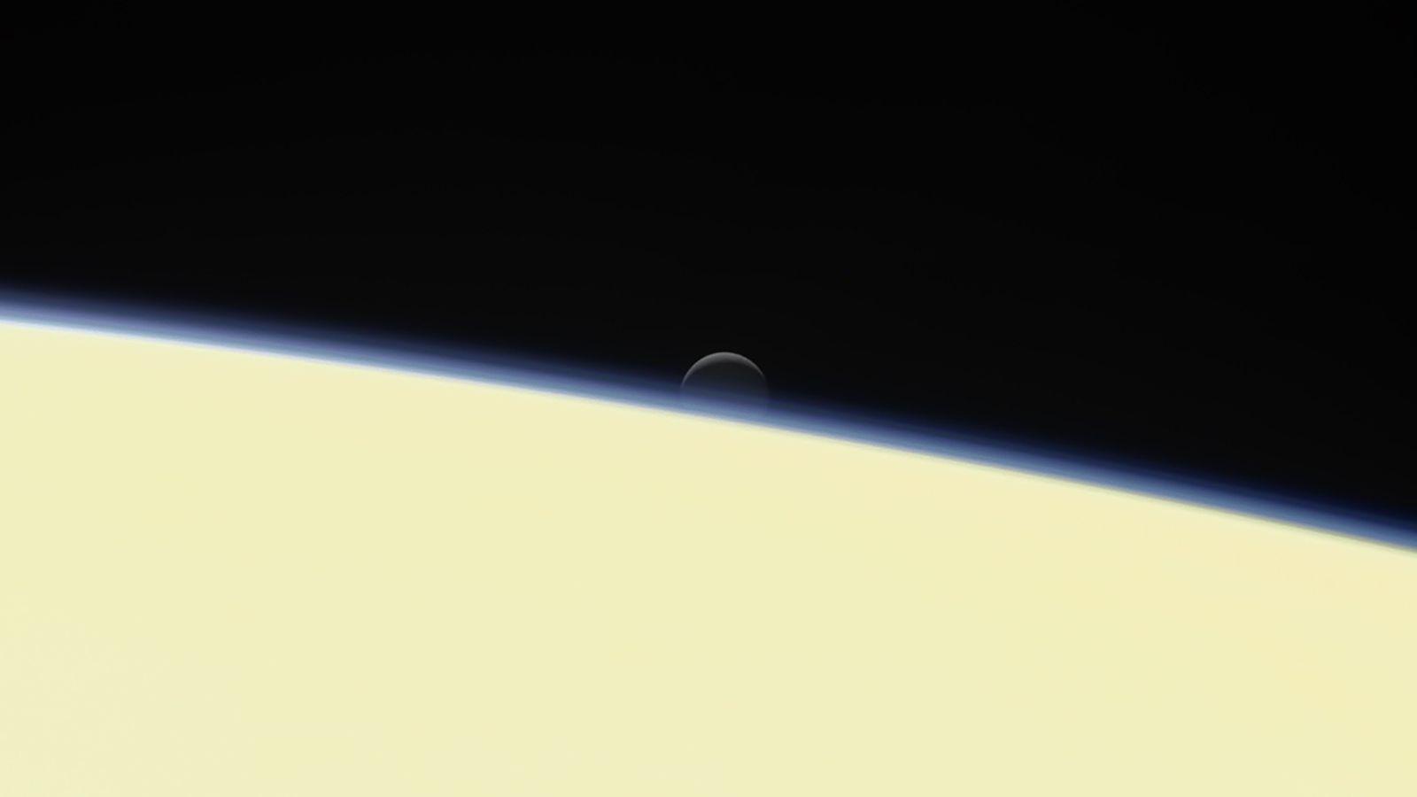 Encélado, a lua gelada de Saturno, se esconde atrás do planeta em um retrato de despedida ...
