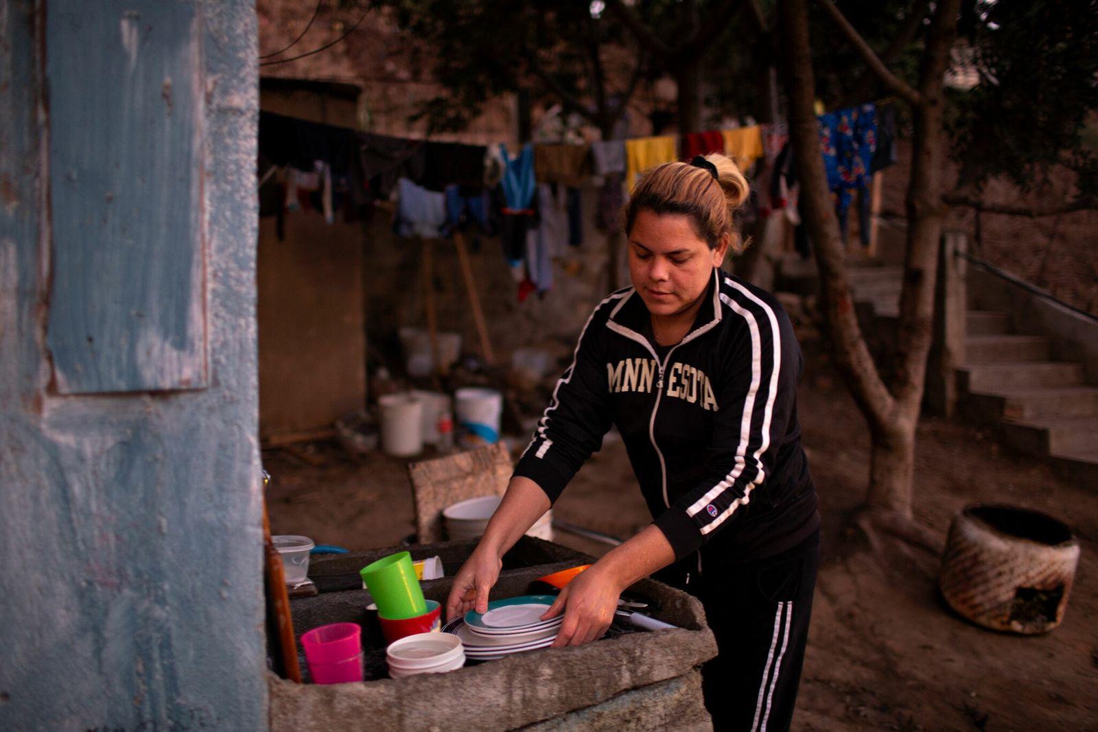 Kataleya lava pratos na pia ao ar livre de seu apartamento em Tijuana.