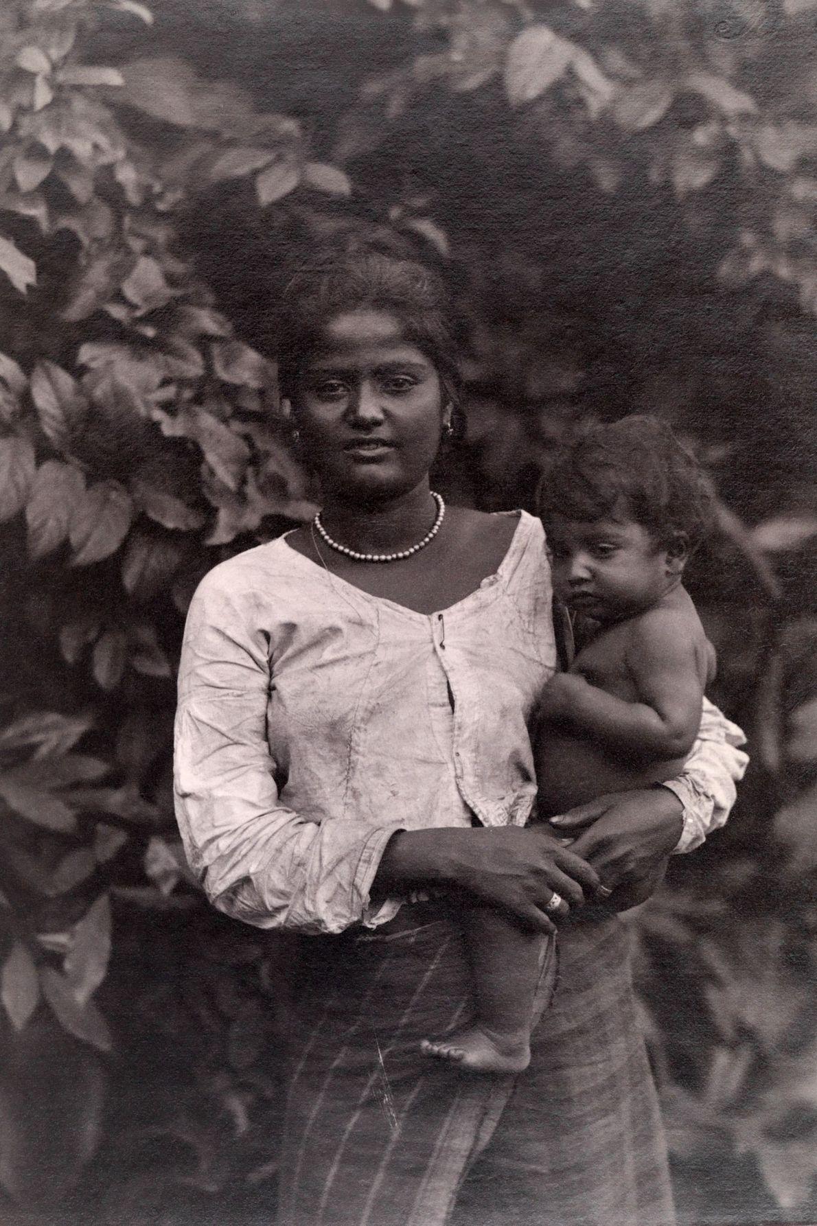 Uma mãe cingalesa apoia uma criança em seu quadril.